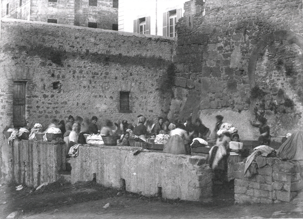 [Ariccia (Italy), women washing clothes beneath a medieval wall]
